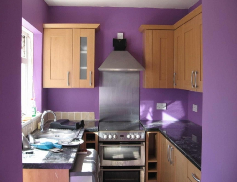 Interior Design In Small Kitchen With Brown Wooden Cabinet And Black Countertop Base Silver Stove Also Purple Painting Wall